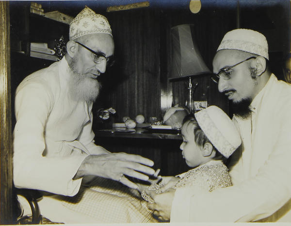 Syedna Burhanuddin bestowing shafaqat on a young Syedna Fakhruddin as Syedna Qutbuddin looks on.